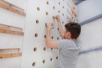 Sporty man climbing on climbing wall. Teenage rock climber in sportswear and equipment.