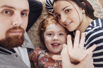 High angle portrait of smiling family lying on carpet at home