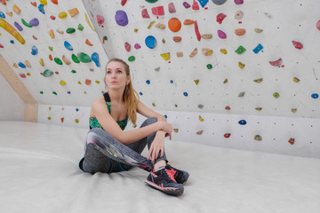 Girl after a workout  rests on the background of the climbing wall.