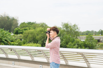 Young asian man taking a photo in city