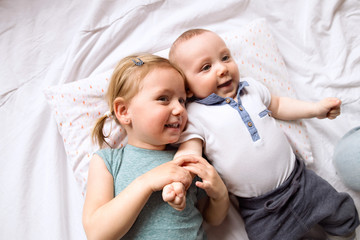 Cute little girl with her baby brother lying on bed.