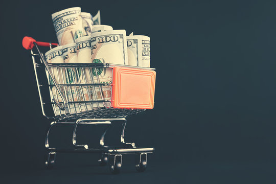 Shopping cart filled with one hundred dollar bill rolls, shallow depth of field, color toning applied.