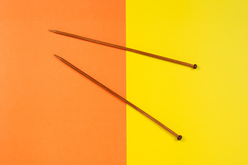 Pair of wooden knitting needles on yellow and orange background