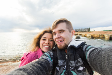 Young laughing couple hiking taking selfie with smart phone. Happy young man and woman taking self portrait with sea or ocean scenery on background. Winter time