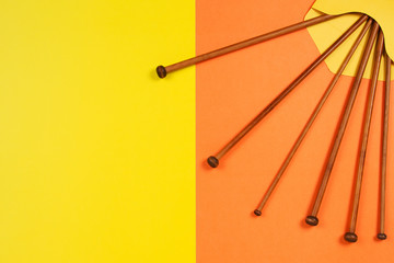 Variety of bamboo knitting needles in envelope on yellow and orange background