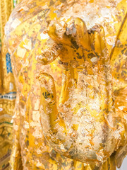 Close up hand filled with gold leaf of statue Buddha. concept shows the devotion of the Buddhists.