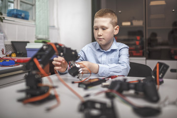 Boy operating machinery at table in classroom