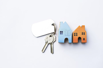 Wooden miniature new house with house key on white background, real estate and property business concept