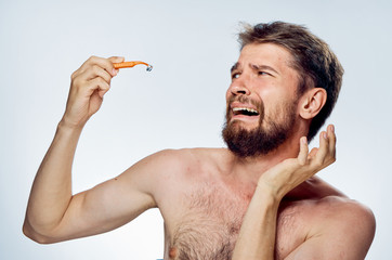 Man with a beard on a white isolated background holds a razor, shave