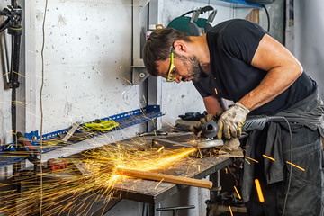 A man welder in a black T-shirt, construction gloves, hard works and brews  grinder metal an angle grinder   in the   garage on a wooden table