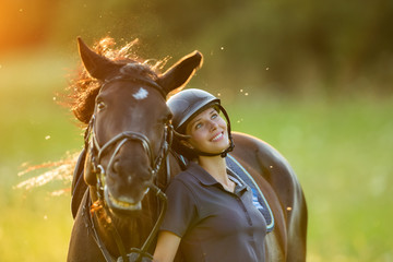 Young woman rider with her horse enjoying good mood
