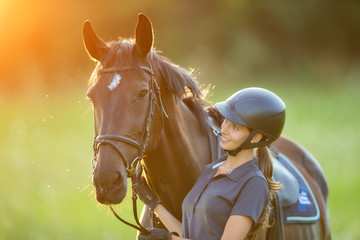 Young woman rider with her horse in evening sunset light