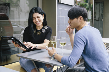 Multiethnic couple in a restaurant looking at phone with a glass of white wine