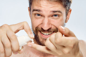 Man with a beard on white isolated background applies cosmetic cream