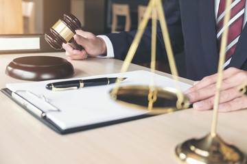 Male lawyer working with gavel and scales of justice, note paper, report the case on wooden table in office, Law and justice concept