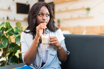 african american woman drinking coffee latte and looking away in cafe