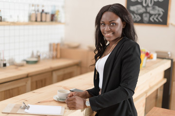 attractive african american woman with coffee cup and bill looking at camera in cafe