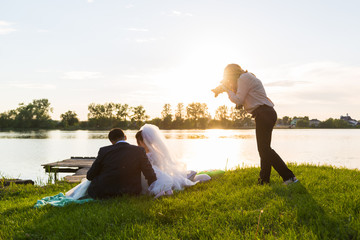 Wedding photographer photographs brides sitting on the lake. Sunset, the sun shines in the camera.