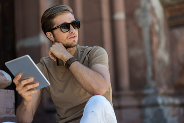 Serious youthful bearded guy using gadget outdoor