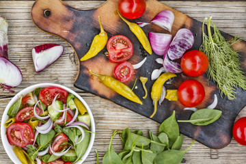 Preparation of vegetable salad. Vegetarian healthy food. Plate with salad. View from above