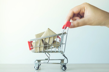 concept of buy shopping, hand of woman pushing Red shopping cart full of gifts box