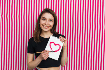 Attractive girl with drawing heart on notebook