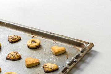 Gebäck Kekse mit Schokolade in Form als Herz liegen dekorativ nach dem Backen auf Backblech