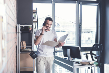 Cheerful adult guy is standing in modern office with smartphone