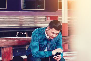 Handsome young asian man looking smart phone and play music with waitting train at station.