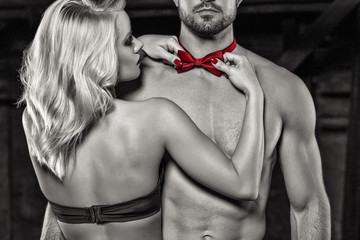 Sensual blonde woman straighten red bow tie on naked sexy man selective coloring