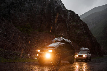 Off-road travel on 4x4 jeep car in mountains. Dangerous dirt road turn Altay cliffs on background. Mountain extreme team of adventurers. Altay mountains, tourist in Siberia, nature views of Russia.