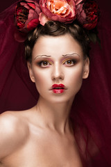 Beautiful girl with art creative make-up in the image of a red bride for Halloween. Beauty face. Photo taken in studio