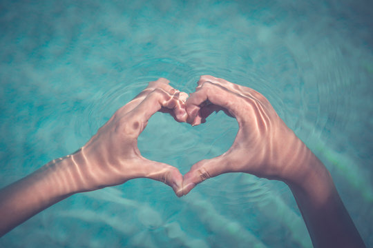Female making heart shape with hands in water