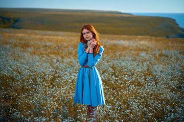 Young beautiful woman in a blue dress is standing in a field of flowers near the sea