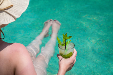 Female relaxing in swimming pool and enjoying the mojito cocktail