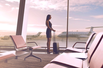 Cheerful gorgeous lady is waiting for flight