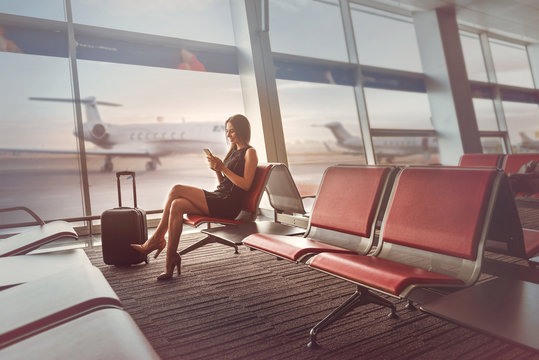 Happy charming lady is sitting on bench at airport