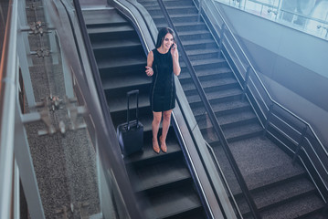 Cheerful graceful lady is talking on mobile phone on moving stairs