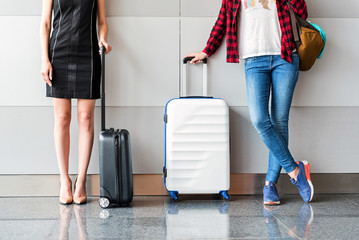 Graceful females are standing in terminal with luggage