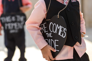 Little boy holds a heart with lettering 'Here comes the bride'