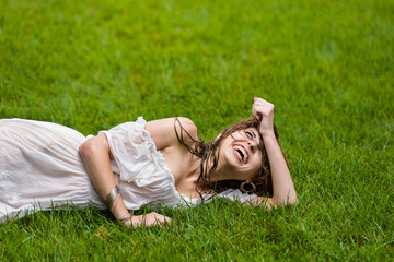 Beautiful woman in white summer dress lays on the grass and has fun with drops, water spray and lawn watering. Summer rain