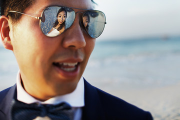 Reflection of cheerful bride in groom's sunglasses