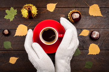 Womans hands holding coffee cup on wooden table with autumn leaves and chestnuts. Autumn background