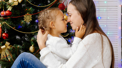 Little girl and mother hugging indoors with christmas tree on the background.