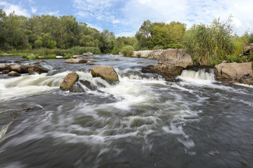 Photo sur Aluminium Rivière de la forêt The rapid flow of the river, rocky coasts, rapids, bright green vegetation and a cloudy blue sky in summer - a frontal view