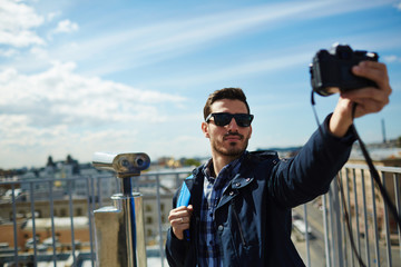 Portrait of handsome young man taking selfie photo while standing on rooftop viewing platform against panoramic city view and coin-operated binoculars in background