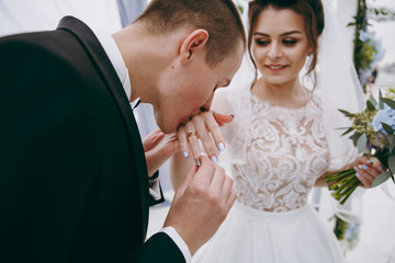 Groom kisses a beautiful bride's hand