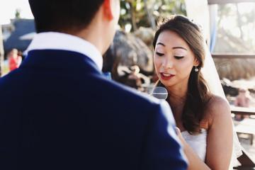 Look over groom's shoulder at bride talking in the microphone