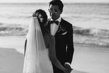 Bride and groom look in each other eyes standing on the beach