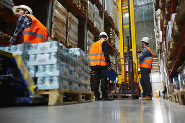 Group of several loaders working in warehouse aisle between tall racks, moving pallets with packed goods